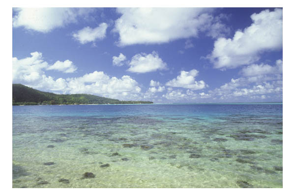Huahine (in Society Island, French Polynesia, S. Pacific)—Clear blue & green calm waters & puffy white clouds