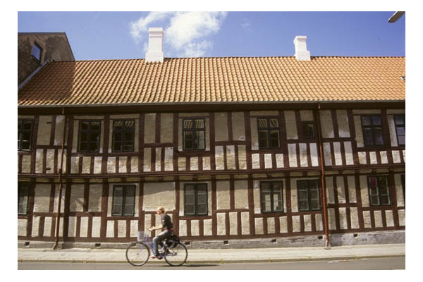 Denmark—Aarhus—in Jutland Peninsula—Half-timbered building with tile roof & bicyclist moving in front.