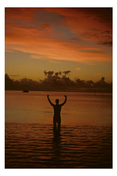 Tahiti (in French Polynesia, S. Pacific)—Man in swimming trunks in water looking at sunset with arms outstretched