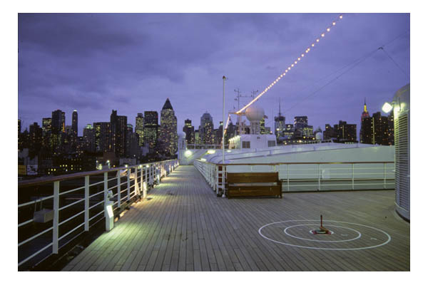 Cruise ship in NY harbor, dusk, with quoits game on open deck