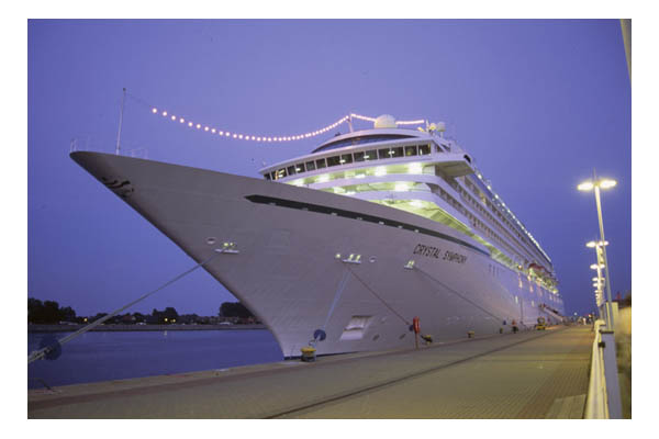 Cruise ship with dress lights tied up in port at dusk, Warmemunde, Germany