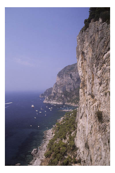 Limestone cliffs and pleasure boats in coves in the Mediterranean Sea, Capri, Italy